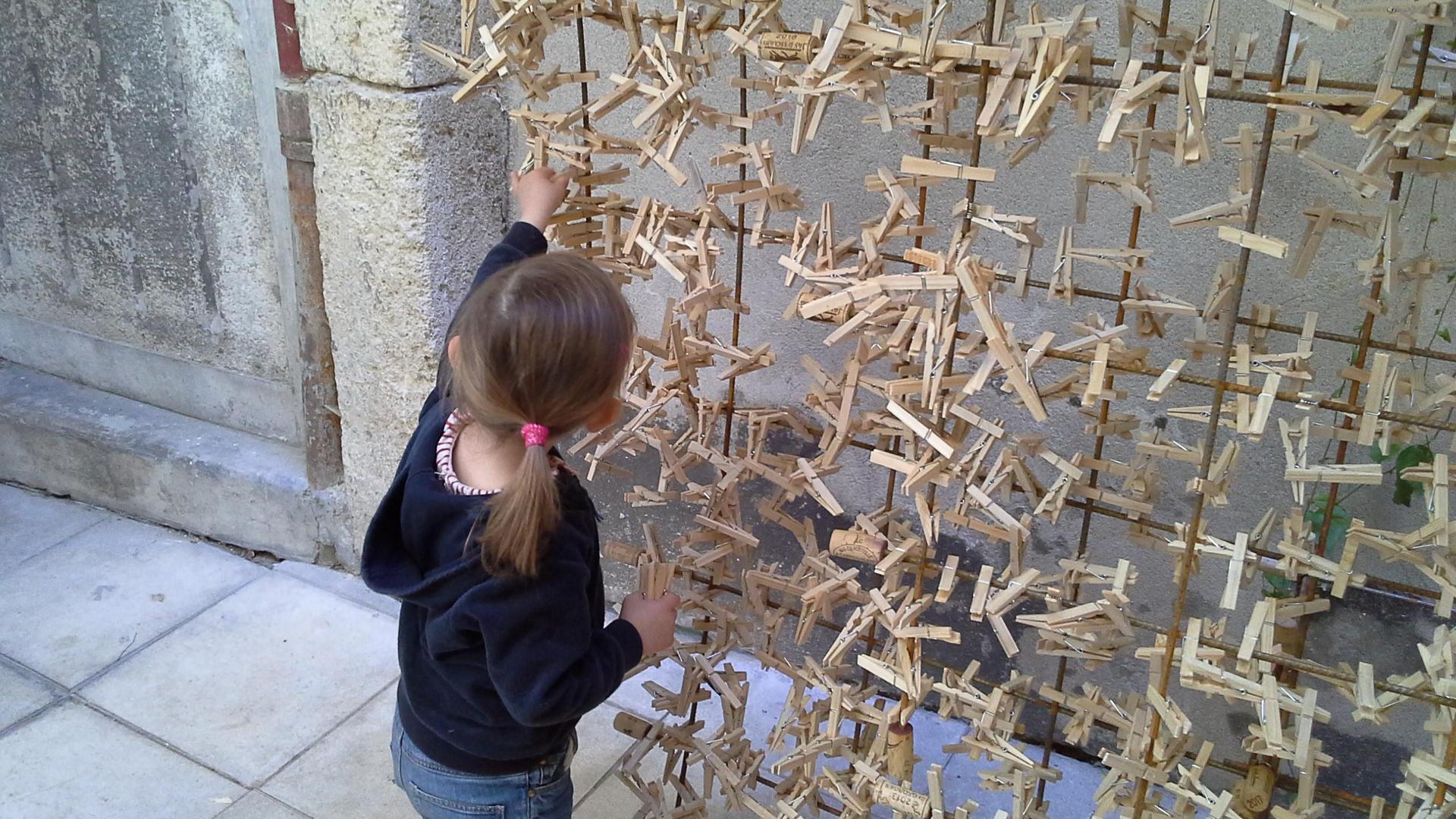 jeune fille jouant avec des fils couverts de pinces à linge