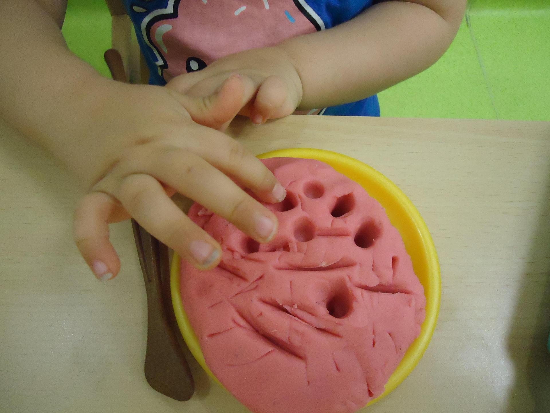 main d'enfant jouant avec de la pate à sel colorée de rose